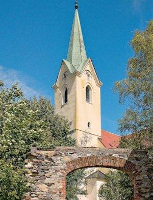 Blick auf den Kirchturm durch den 1877 geschaffenen Durchbruch zum neuen Friedhof